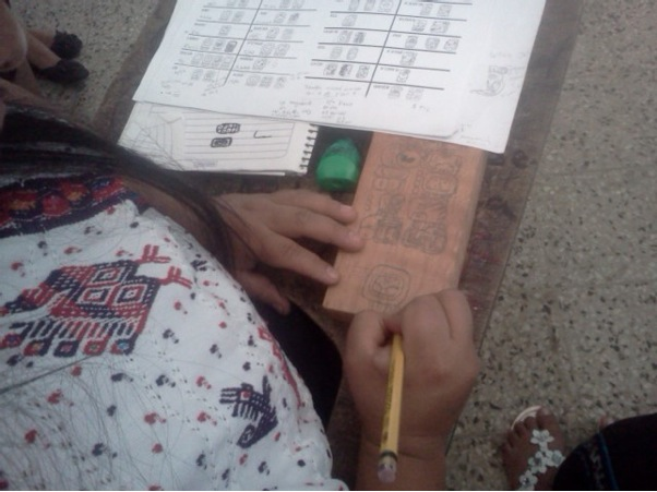Member of the Poqomam Community writing her text on a piece of wood.