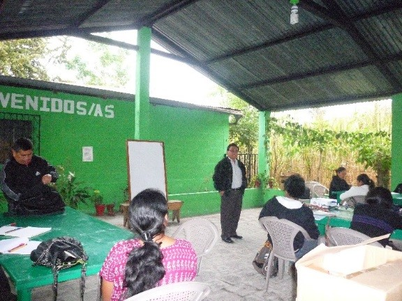 Andrés Cholotío (in front) gives instruction; Alejandro Teletor Velásquez (left) president Achí Linguistic Community.