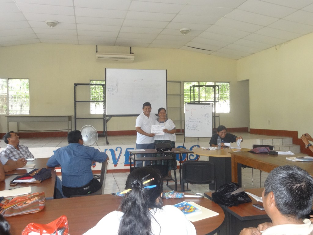 Romel Reyes, Director of Defensoría Q'eqchi', delivering a certificate of participation for one of the teachers.