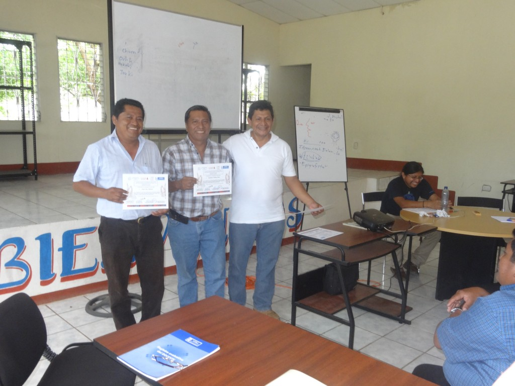 Romel Reyes, Director of Defensoría Q'eqchi', delivering certificates of participation to two teachers.