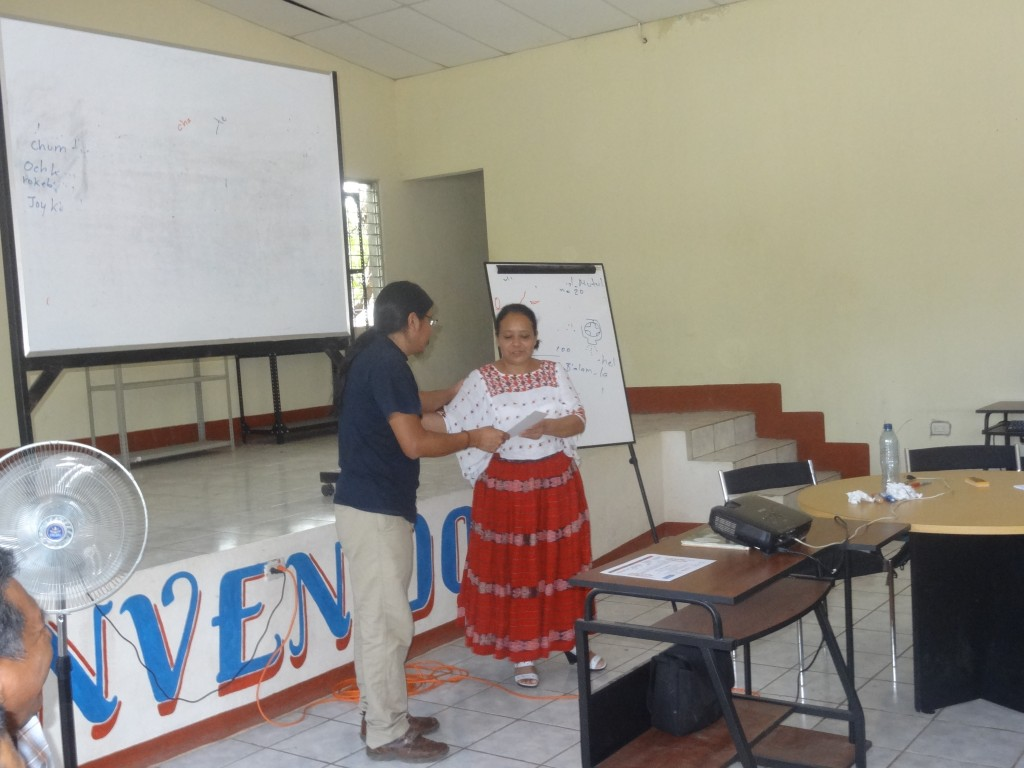 Hector Xol, workshop facilitator, delivering a certificate of participation to one of the participating teachers.